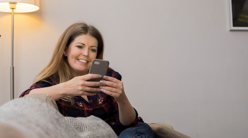 Woman sits on couch using her phone to pay rent